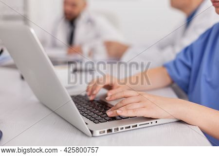 Close-up Of Practitioner Woman Nurse Hand Typing Sickness Treatment On Laptop Computer Working In Co