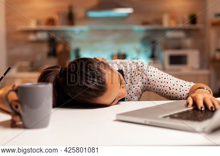 Freelance Woman Falling Asleep In Home Kitchen Working Overtime On A Project. Employee Using Modern