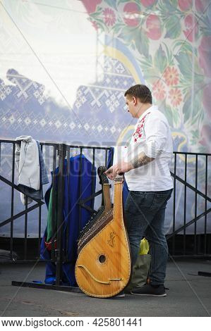 A Series Of Photographs With Ukrainian Costumes. Man In A Ukrainian Embroidered Shirt With A Kobza.