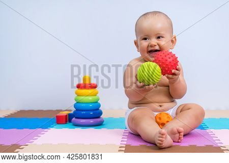 Happy Newborn Baby Playing With Rubber Balls In Playroom