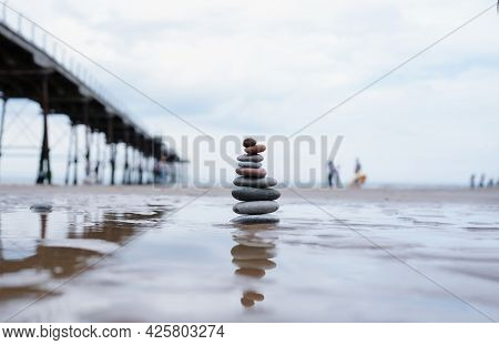Pebble Tower By Seaside With Blurry Pier Down To The Sea, Stack Of Zen Rock Stones On The Sand, Ston