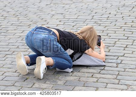Girl Photographer In Jeans Taking Pictures On Smartphone Kneeling Down On The Street. Woman Tourist,