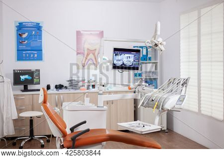 Dental Chair And Other Accesorries Used By Dentist In Empty Cabinet. Stomatology Cabinet With Nobody