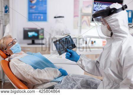 Stomatolog In Safety Gear Agasint Coronavirus Holding X-ray Pf Senior Patient. Elderly Woman In Prot