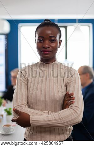 Successful Smiling African Business Woman Holding Arms Crossed Looking Atcamera In Conference Room.
