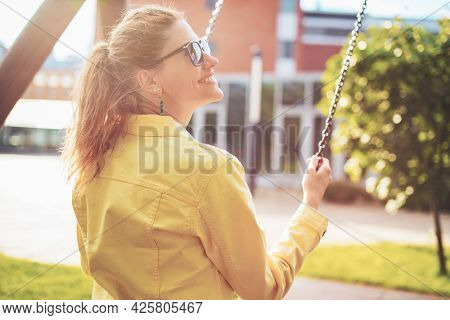 Happy Young Positive Woman On Swing In Sunset, Profile View, Outdoors In Park