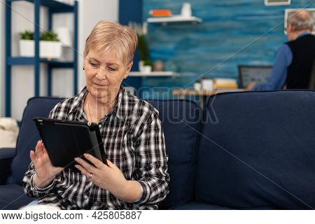 Happy Elderly Lady Waving At Smartphone During Video Call. Senior Woman Waving At Phone Webcam In Th