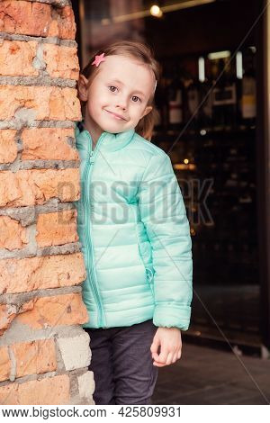 Portrait Of A Little Caucasian Blonde Girl Near A Brick Wall Looking At The Camera.