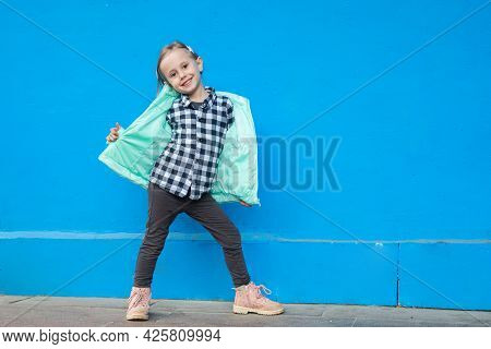 Cute Little Caucasian Girl Posing On A Wooden Deck Next To A Blue Wall Looking At The Camera
