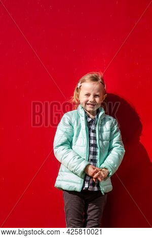 Adorable Little Caucasian Girl Sitting On A Wooden Deck Next To A Red Wall Looking At The Camera