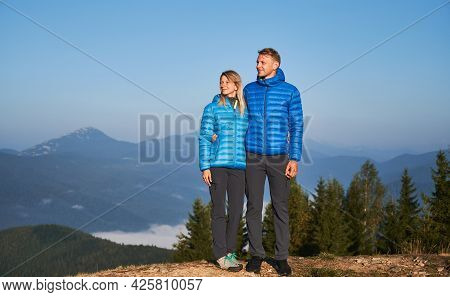 Full Length View Of Couple Of Travelers While Walking On Mountain Hills Stopped At Top Of One Of The