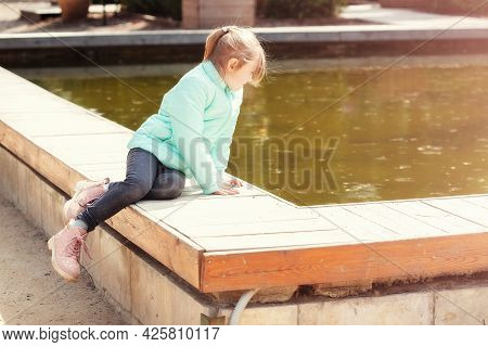 Lonely Little Caucasian Girl Sitting By The Lake Water And Looking At The Water. Water Surface Of Th