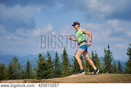 Side View Of Guy Running In Fresh Air By Mountain Trails. Summer Trail Running Marathon In Mountains