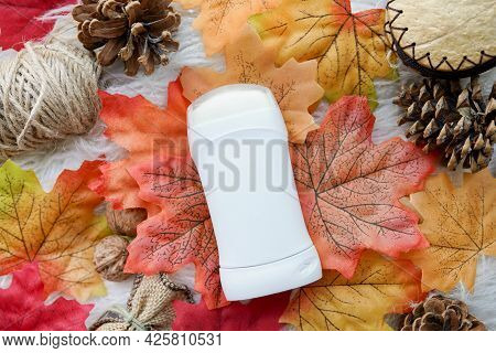 White Deodorant With Autumn Composition Of Fall Leaves And Cones On White Background . Natural Skin