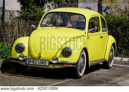 Bucharest, Romania, 2 April 2021 Old Retro Yellow Volkswagen Beetle Classic Car Parked A Street In A