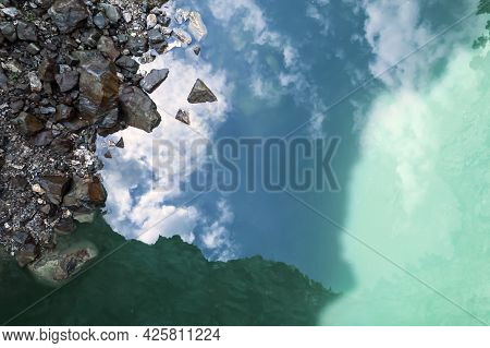 Green Turquoise Water And Reflections Of The Sky In It. Natural Natural Background. Rocks And Clouds