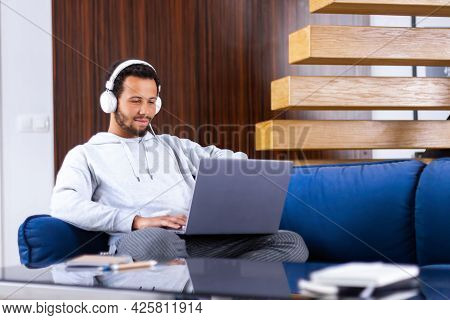 Online Tutoring Concept. Confident And Clever African Man Wearing Headphones Is Watching Classes Web