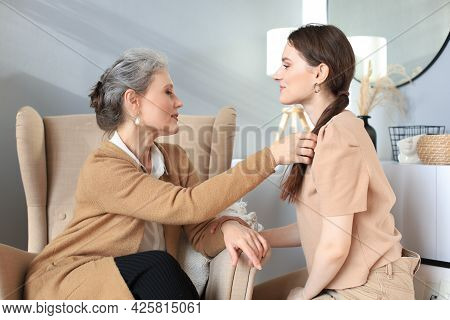 Happy Elderly Middle Mother Sitting On Chair Touching A Strand Of Daughter's Hair, Looking Each Othe