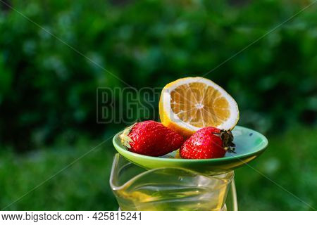 Defocus Saucer With Lemon And Two Strawberry Standing On Glass Jug Of Lemonade On Nature Green Backg