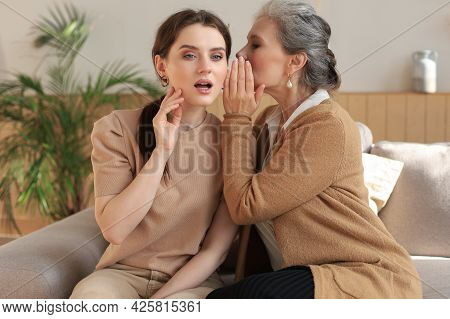 Happy Middle Mother Whispering Secret To Her Smiling Daughter At Home, Gossiping, Sharing Secret. Be