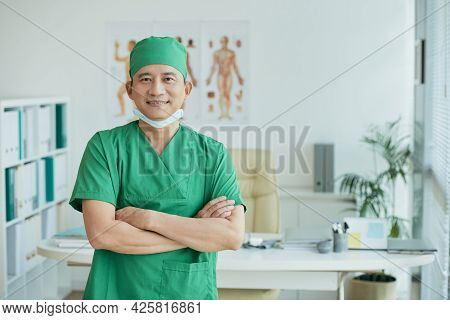 Smiling Experienced Surgeon In Green Scrubs And Medical Mask Standing In Office Of Clinic And Lookin