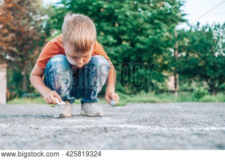 The Child Drawing On The Sidewalk. The Face And Clothes Are Stained With Chalk.