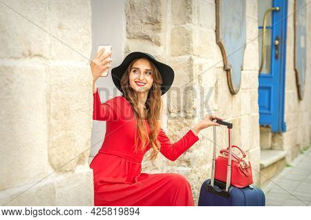 Beautiful Young Caucasian Woman In Black Hat Looking On The Smartphone Smiling And Sitting On Stairs