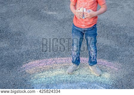 Child Holding Colored Chalk In His Hands And Dirty T-shirt In Front