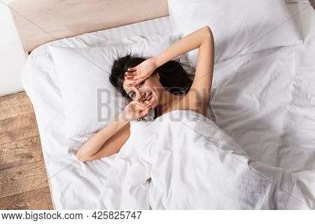 Top View Of Young Shy Woman Lying Under Blanket And Smiling In Bedroom