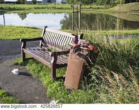 Wooden Bench In A Park With A Pond And An Overflowing Trash Can Next To It Full Of Bags Of Dog Poop