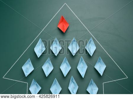 Group Of Paper Boats On A Green Background. Concept Of A Strong Leader In A Team, Manipulation Of Th