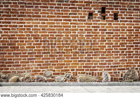 Old Weathered Wall Of Bricks And A Sidewalk