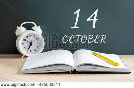 October 14. 14-th Day Of The Month, Calendar Date.a White Alarm Clock, An Open Notebook With Blank P