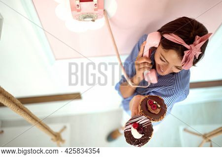 Closeup from above of a young beautiful girl chatting on the phone in a pleasant atmosphere in a retro looking pastry shop while holding chocolate donuts in her hand. Pastry shop, dessert, sweet