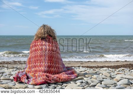 Mature Woman In Fifties Sitting On A Rocky Beach Looking To The Ocean