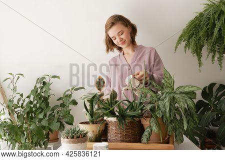 Cute Girl Watering Beautiful Indoor Green Plants Growing In Different Pots.