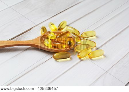 Fish Oil Capsules On Wooden Background And Texture, Fish Oil Capsule Placed On A Wooden Spoon, Spot