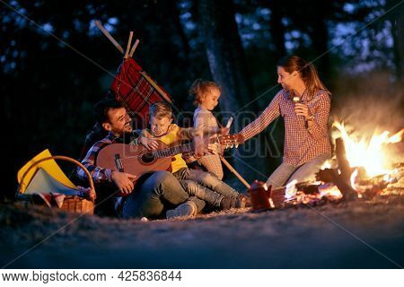 A young happy family having playing around a campfire in the forest in a beautiful night