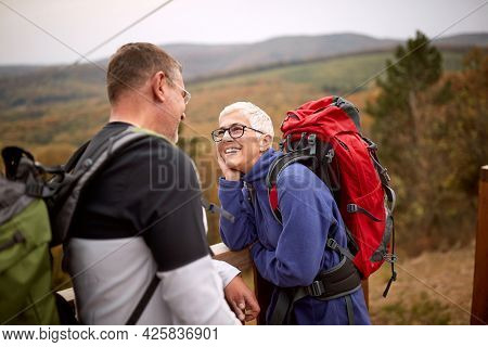 An elderly couple in love enjoying the view from the top of a watchtower on a beautiful autumn day