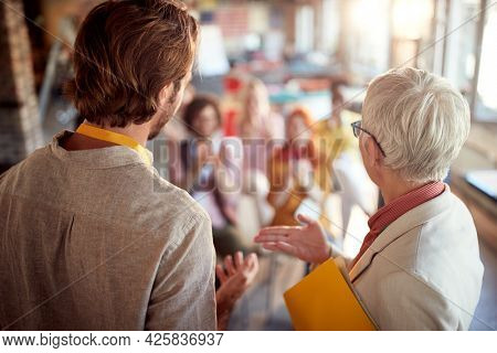 An elderly female boss is introducing her colleague who will held a presentation for employees in a pleasant atmosphere