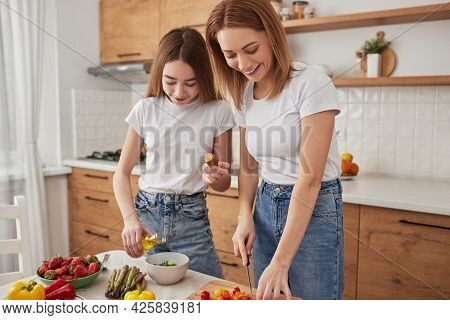 Positive Adult Woman With Preteen Daughter Preparing Healthy Vegetarian Meal With Fresh Ingredients