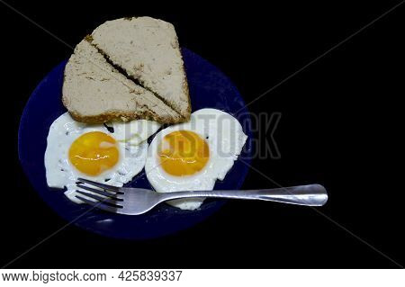 Fried Eggs And Bread Spread With Pate On A Blue Plate On A Black Background