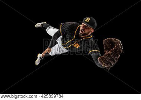 Flying. Baseball Player, Catcher In Sports Uniform And Equipment Practicing Isolated On A Black Stud