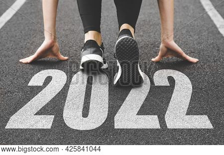Close-up Of Female Feet In Sneakers At The Start. Beginning And Start Of The New Year 2022, Goals An