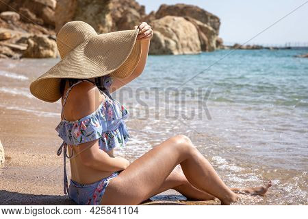 An Attractive Young Woman Sits On The Seashore In A Swimsuit And A Large Hat And Sunbathes.