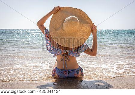 A Woman In A Big Hat Sunbathes On The Beach Near The Sea.