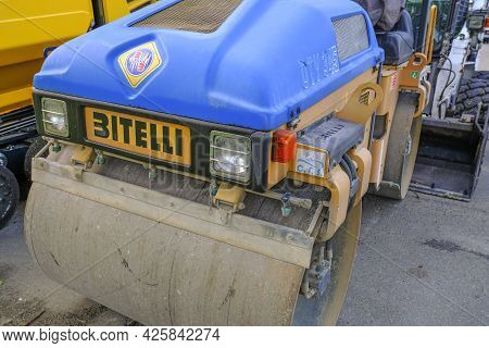 May 2021 Parma, Italy: Blue Asphalt Paver Road Machine Bitelli Parked Across Other Heavy Industrial