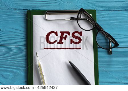 Cfs (chronic Fatigue Syndrome) - Acronym In A Notepad On A Blue Background With A Pen, Glasses And A