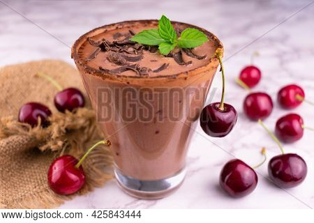 Chocolate Smoothie With Cherries Garnished With A Mint Leaf. Close-up.