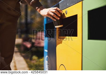 Person Throwing Her Coffee Cup Into Rubbish Bin For Plastic